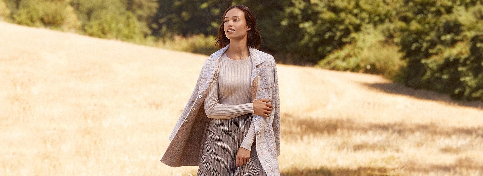 Eine Frau in einem beigen Outfit auf einem Feld
