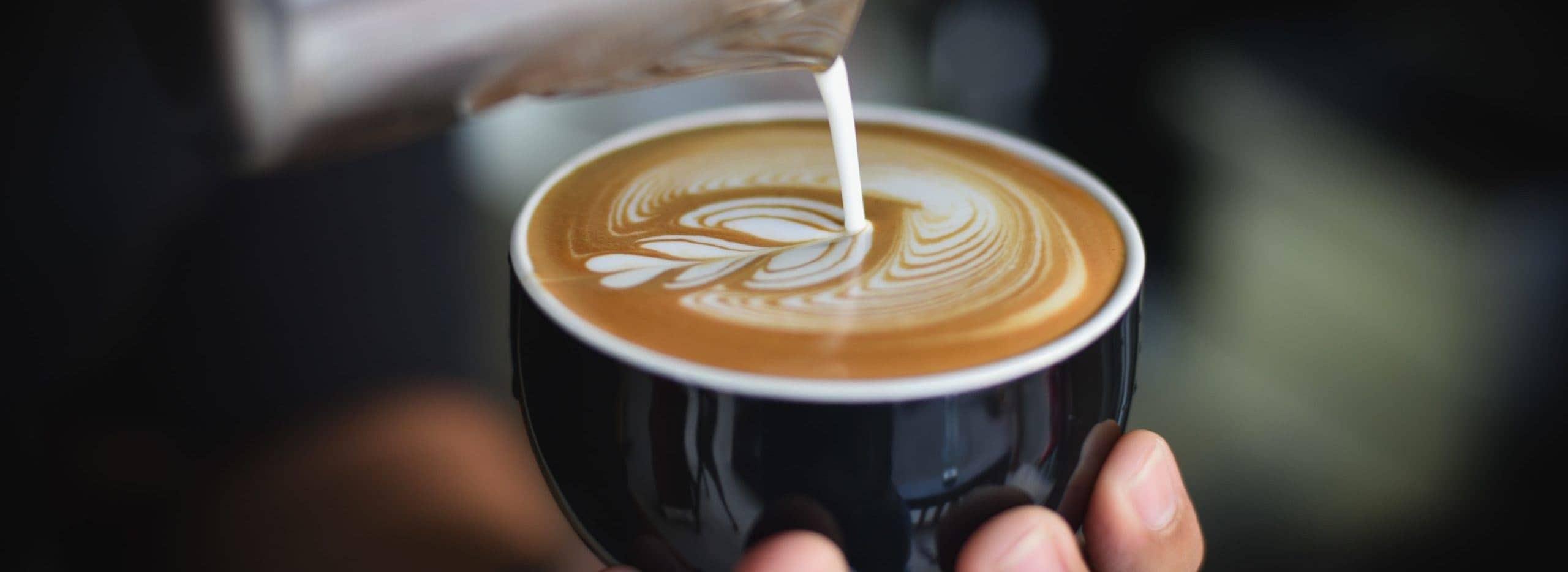 Eine Person giesst Milchschaum in einen Cappuccino