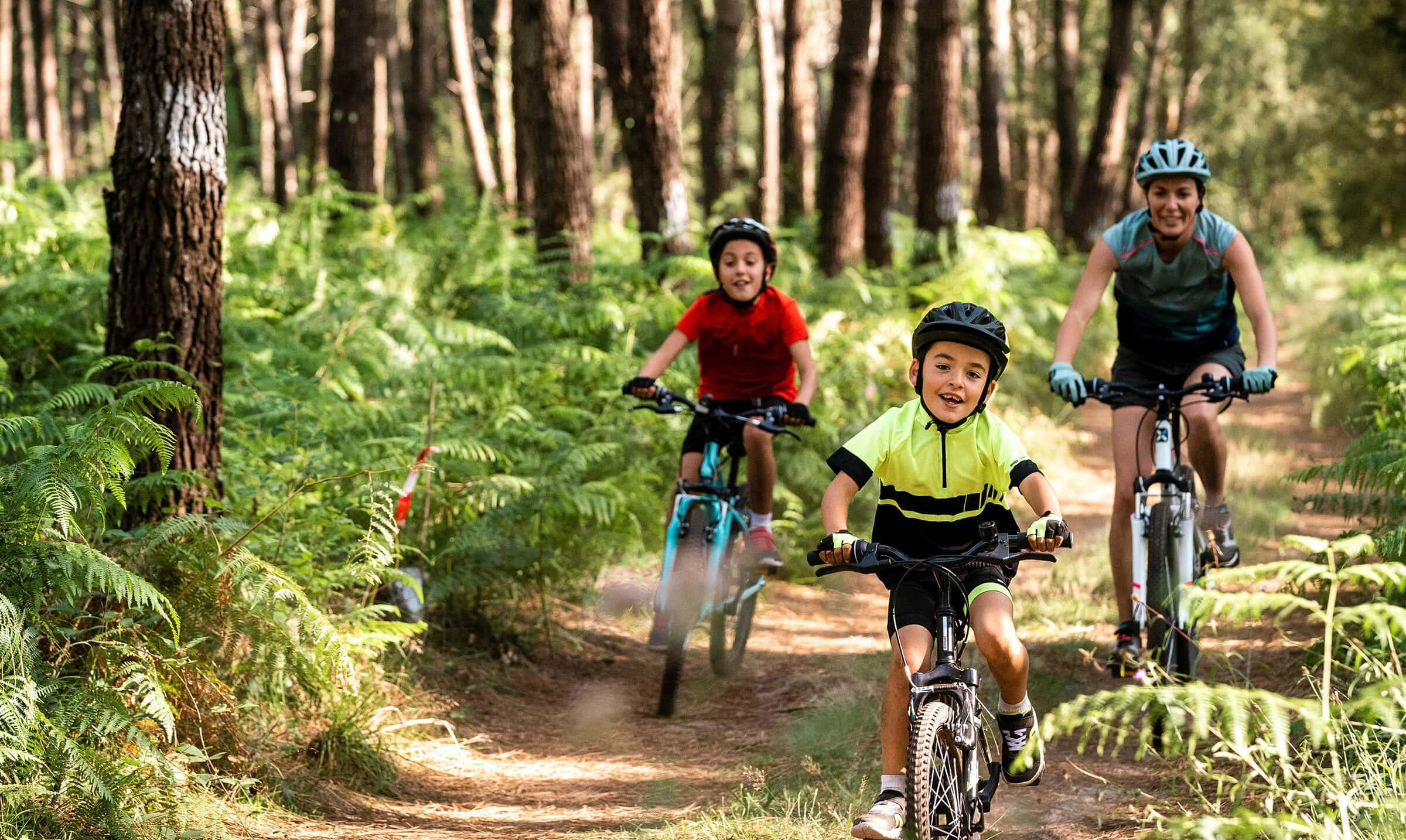 Eine Frau fährt mit zwei Kindern auf Bikes durch den Wald