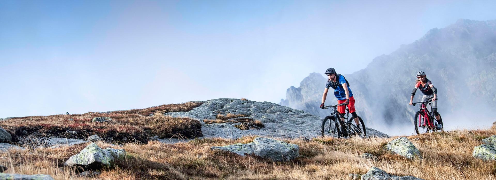 Ein Mann und eine Frau beim Biken in den Bergen
