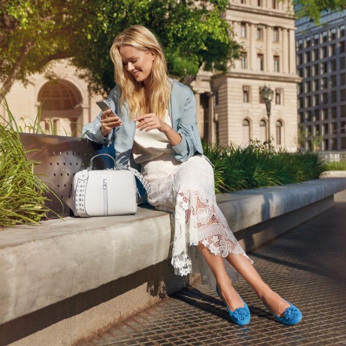 Eine stylish angezogene blonde Frau sitzt auf einer Bank und schaut auf ihr Handy