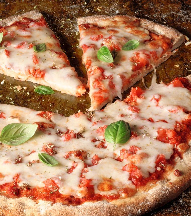 Eine Pizza Margherita mit Basilikumblättern