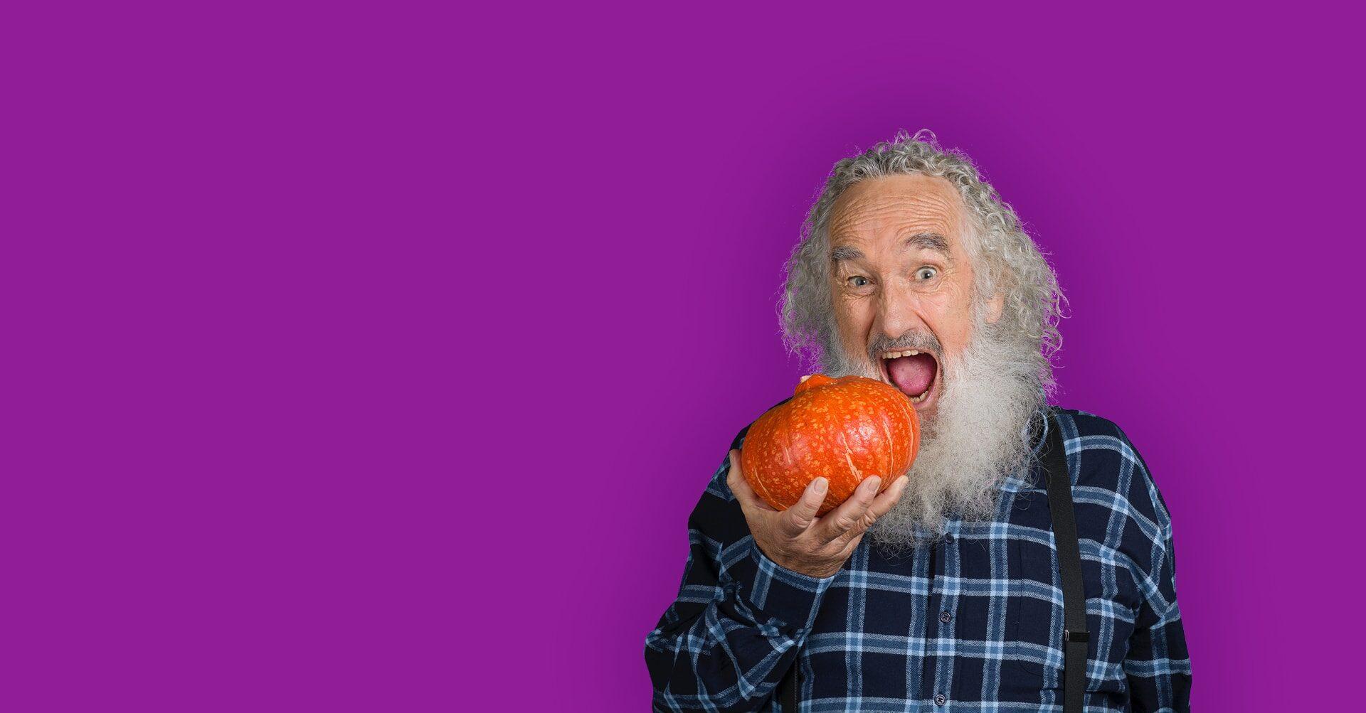 Alter Mann mit Bart will in einen Kürbis beissen