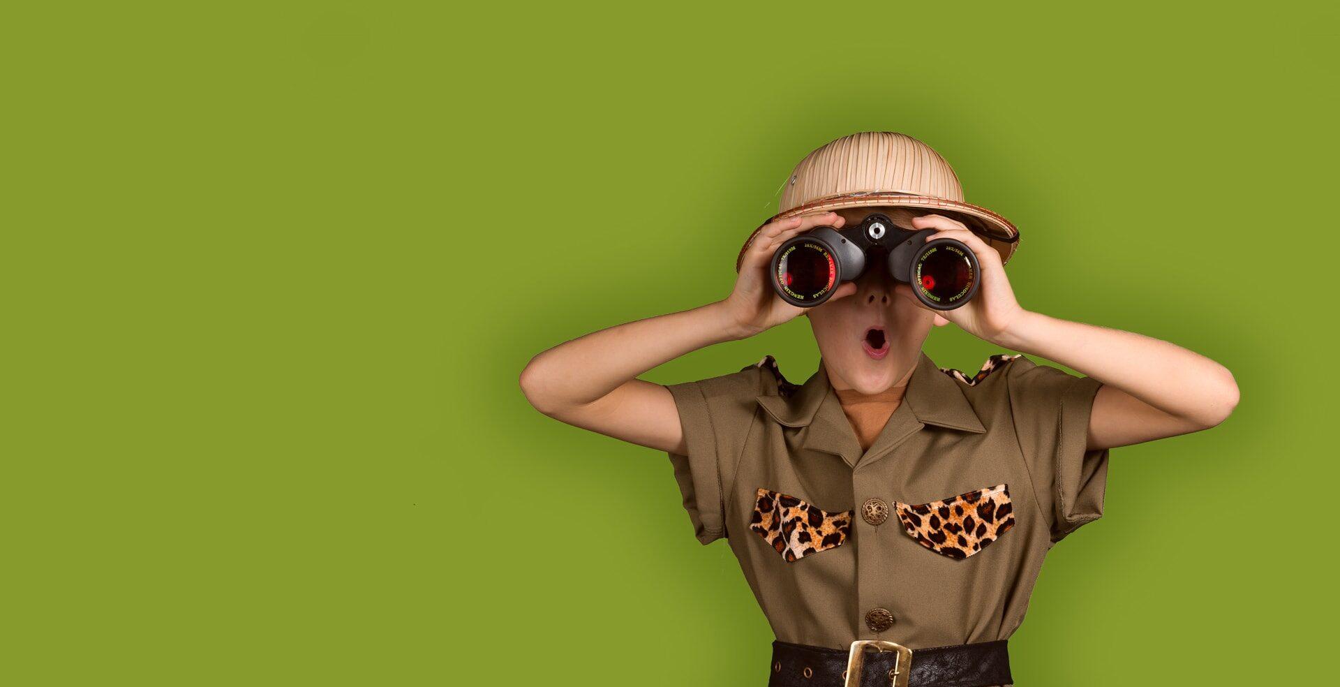 Ein Junge in einem Safarioutfit schaut durch ein Fernglas