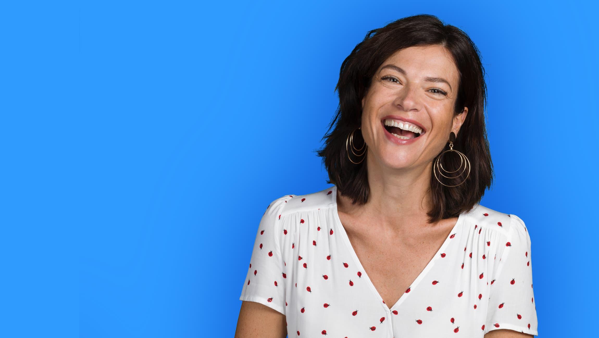 Lachende Frau in einem weissen Kleid mit Muster