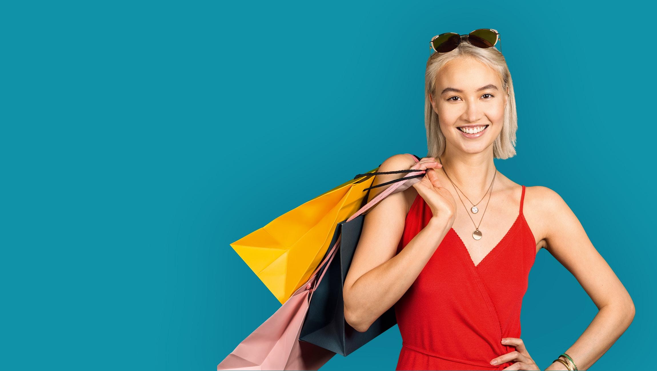 Junge Frau in Sommerkleid und mit Sonnenbrille trägt mehrere Einkaufstaschen