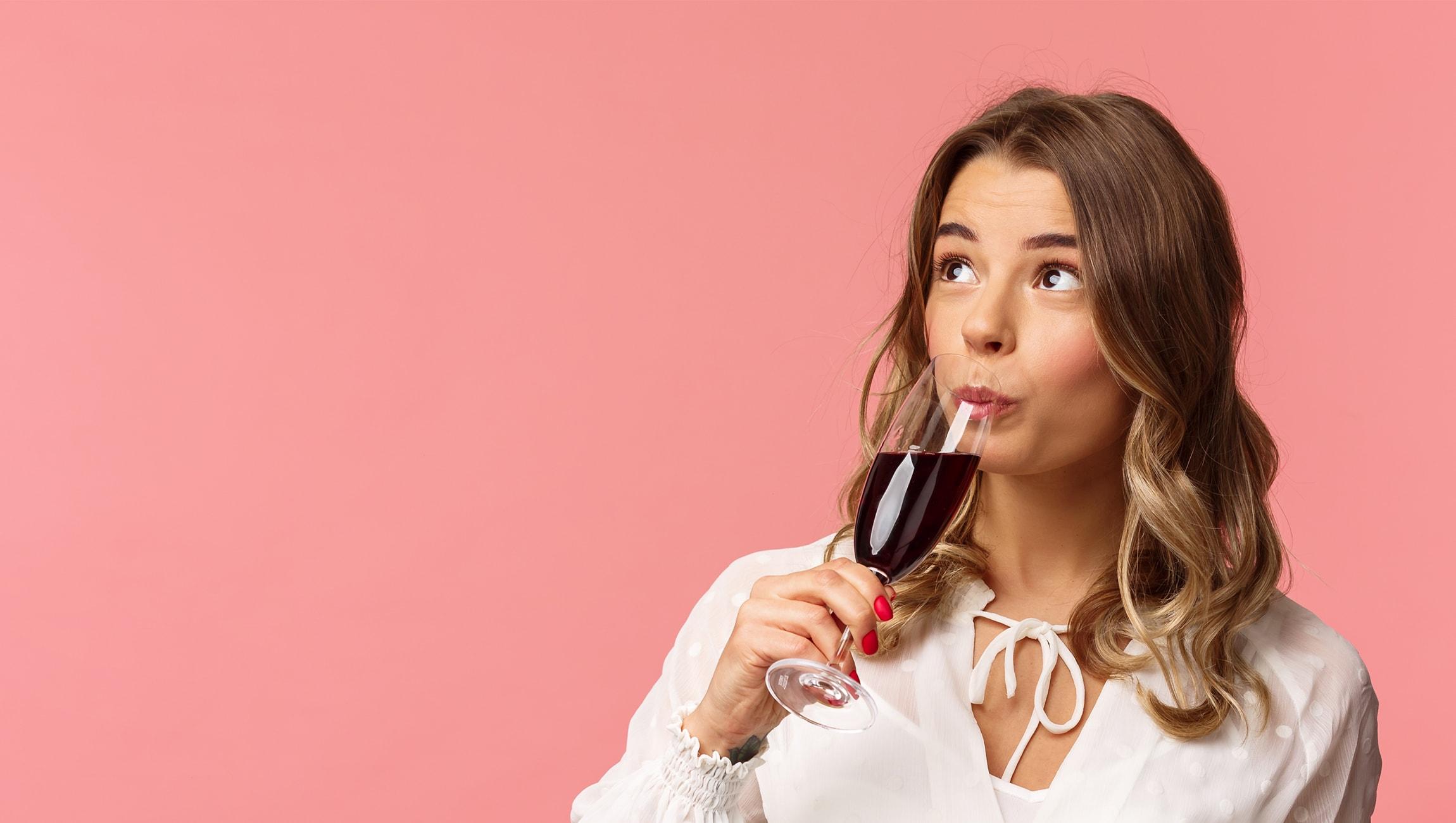 Junge Frau hebt ein Glas Wein an ihren Mund