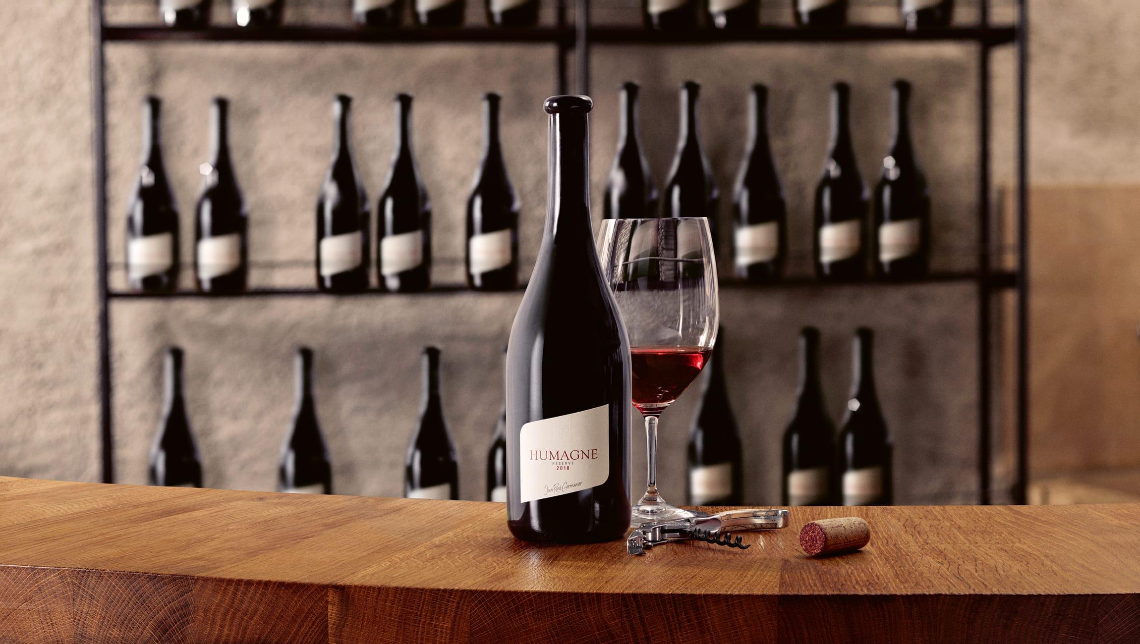 Eine Weinflasche und ein Weinglas vor einem Weinregal